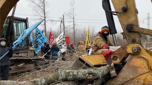 A Water Protector chains himself to construction equipment at the Line 3 Enbridge pipeline site. (Photo courtesy Ginew Collective)