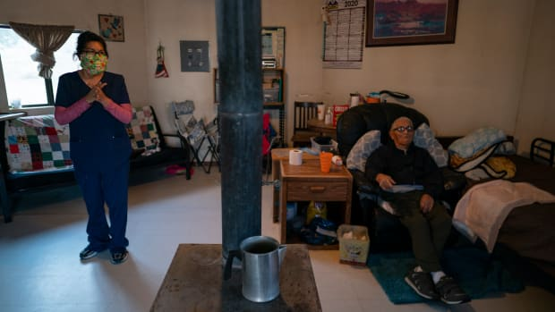 Mabel Charley, left, applies hand sanitizer as she arrives to care for her home-bound uncle in his hogan, a traditional Navajo dwelling, in Chilchinbeto, Ariz., on the Navajo reservation on April 21, 2020. The Navajo reservation has some of the highest rates of coronavirus in the country. If Navajos are susceptible to the virus' spread in part because they are so closely knit, that's also how many believe they will beat it. (AP Photo/Carolyn Kaster)