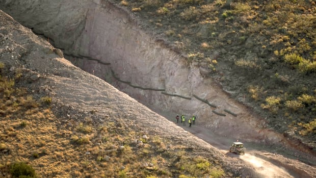 With Mexico to the right, crews stand in a pathway cleared by explosives to make way for border wall construction, Wednesday, Dec. 9, 2020, in Guadalupe Canyon, Ariz. Construction of the border wall, mostly in government owned wildlife refuges and Indigenous territory, has led to environmental damage and the scarring of unique desert and mountain landscapes that conservationists fear could be irreversible. (AP Photo/Matt York)