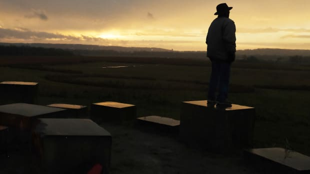 Guy Jones takes in the setting sun at the Hopeton Earthworks during the winter solstice. (Photo by Mary Annette Pember)
