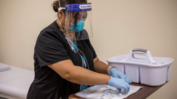 In this Tuesday, Dec. 29, 2020, photo provided by Johns Hopkins Center for American Indian Health, registered nurse Starla Garcia prepares a coronavirus vaccine in Chinle, Ariz., for someone who enrolled in the COVID-19 vaccine trials on the Navajo Nation and initially received a placebo. (Nina Mayer Ritchie/Johns Hopkins Center for American Indian Health via AP)