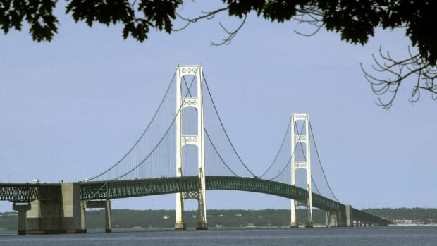 This July 19, 2002, file photo, shows the Mackinac Bridge that spans the Straits of Mackinac from Mackinaw City, Mich. Supporters and opponents of a proposed oil pipeline tunnel beneath the Great Lakes channel are making their case to federal officials. The Army Corps of Engineers hosted an online public hearing Monday, Jan. 11, 2021, on Enbridge's application for a permit. The Canadian pipeline company wants to drill a nearly 4-mile (6.4-kilometer) tunnel through bedrock under the Straits of Mackinac that would house a replacement for twin pipes that have run along the bottom of the waterway connecting Lake Huron and Lake Michigan for 67 years.(AP Photo/Carlos Osorio, File)