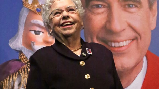 """Joanne Rogers stands in front of a giant Mister Rogers Forever Stamp following the first-day-of-issue dedication in Pittsburgh on March 23, 2018. Rogers, the widow of Fred Rogers, the gentle TV host who entertained and educated generations of preschoolers on """"Mister Rogers' Neighborhood,"""" has died. She was 92. (AP Photo/Gene J. Puskar, File)"""