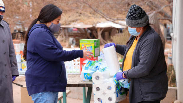 Miyoshi Lee, left, and Leslie Goldtooth, right, aid residents with some basic relief goods at the Full Circle Intertribal Center in Moab, Utah on Dec. 17, 2020. They said joining the group has helped them find a sense of community, where they've both lived for over two decades. The Utah-based nonprofit was founded to help build community among the Native population in Moab and has recently turned its attention to caring for Native elders during the coronavirus pandemic. (Kate Groetzinger/KUER, via AP)