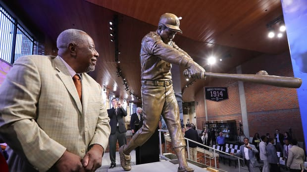 In this March 29, 2017, file photo, Hank Aaron looks at his new statue in Monument Garden at SunTrust Park, home of the Atlanta Braves, after the unveiling ceremony in Atlanta. Hank Aaron, who endured racist threats with stoic dignity during his pursuit of Babe Ruth but went on to break the career home run record in the pre-steroids era, died early Friday, Jan. 22, 2021. He was 86. The Atlanta Braves said Aaron died peacefully in his sleep. No cause of death was given. (Curtis Compton/Atlanta Journal-Constitution via AP, File)