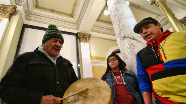 In this Feb. 18, 2020, file photo, a protester plays a drum and sings while joined by other Native American protesters opposing the Keystone XL Pipeline at the South Dakota Capitol in Pierre. Major construction projects moving forward along the U.S. borders with Canada and Mexico amid the coronavirus pandemic are raising fears workers could spread infections within nearby communities, including several Native American tribes. (AP Photo/Stephen Groves)