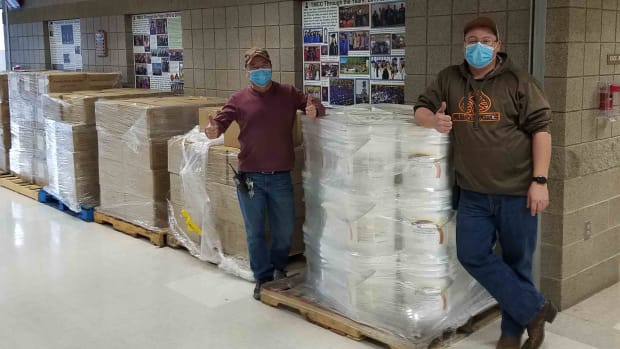 Albert Gourneau (left) and Anthony Desjarlais (right), from Turtle Mountain Community College's facilities department, prepare to distribute sanitizing supplies and safety equipment at the tribal college campus in Belcourt, North Dakota. (Photo courtesy of Dina Horwedel)