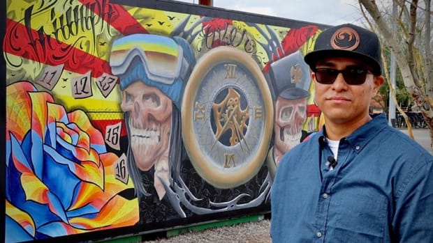 """Jesse Yazzie is a Navajo artist and the first of four creatives who will exhibit their artwork quarterly on a 8X20-foot shipping container near the Roosevelt Row Welcome Center. Behind him is his mural """"Triumph Over Tragedy."""" (Photo by Eunique Yazzie/KJZZ)"""