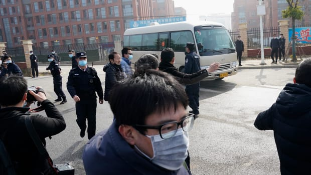Journalists and security personnel gather near the entrance of the Wuhan Institute of Virology after a visit by the World Health Organization team in Wuhan in China's Hubei province on Wednesday, Feb. 3, 2021. (AP Photo/Ng Han Guan)