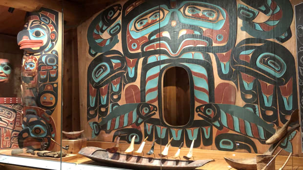 Panel by Nathan P. Jackson, Tlingit. An upright, three panel sculpture with iridescent side panels and the middle panel carved into an angular turquoise face with big blue eyes, thick black brows, and a burgundy beak. Orange feathers with black tips stand along the top. Raven & Dog Salmon, 2019. Western red cedar, exterior latex house paint, dimensions 11 × 7 feet. Photo by Shar Fox.