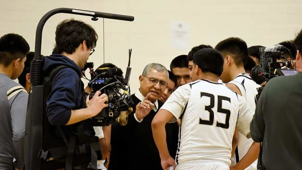 """A Netflix crewmember gets footage of Chinle basketball coach Raul Mendoza talking to his team during filming of the documentary """"Basketball or Nothing,"""" in this file photo last year. The film was chosen as the best sports documentary at the 11th Annual Realscreen Awards ceremony. (Photo courtesy of Navajo Times)"""