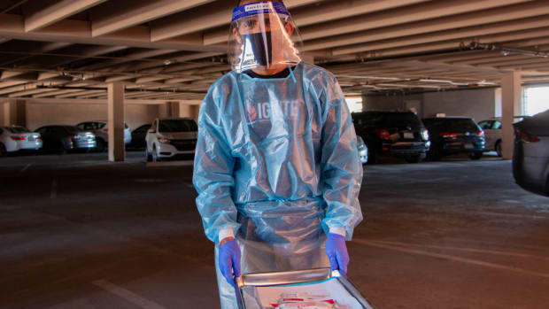 Christopher Carrillo, a clinical tester at the Southwest Center for HIV/AIDS in Phoenix, rolls a cart through the center's parking garage for drive-thru HIV finger prick tests. (Photo by Gianluca D'Elia/Special for Cronkite News)