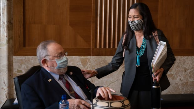 Rep. Deb Haaland, D-New Mexico, delivers a gift to Rep. Don Young, R-Alaska, before the start of the Senate Committee on Energy and Natural Resources hearing on her nomination to be Interior Secretary, Tuesday, Feb. 23, 2021 on Capitol Hill in Washington. (Jim Watson/Pool via AP)