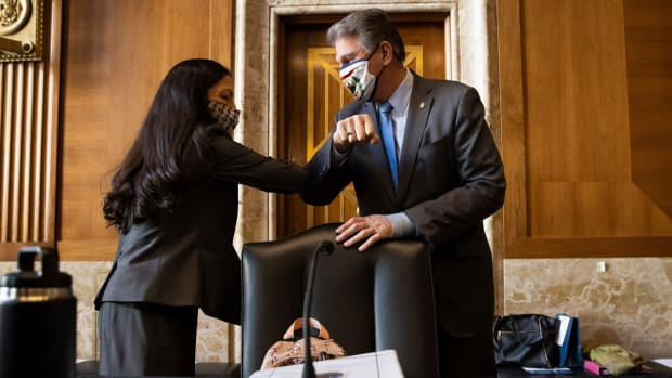 Sen. Joe Manchin, D-West Virginia, greets Rep. Deb Haaland, D-New Mexico, before the start of the Senate Committee on Energy and Natural Resources hearing on her nomination to be Interior Secretary, Tuesday, Feb. 23, 2021 on Capitol Hill in Washington. (Graeme Jennings/Pool via AP)