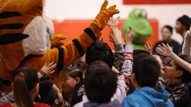 Children surround a mascot with the BEAR Program during a local performance. (The Bears on Pine Ridge)