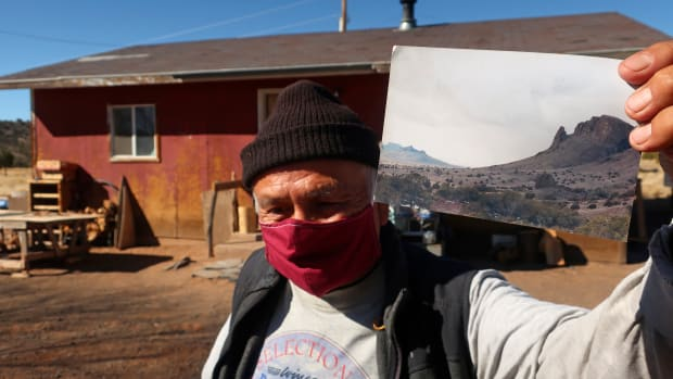"""Raymond Clark displays a photo of a geographic feature known as the """"Praying Mountain"""" outside his home in Teesto, Ariz., on the Navajo Nation, on Thursday, Feb. 11, 2021. Teesto workers, health representatives, volunteers and neighbors keep close tabs on another to ensure the most vulnerable citizens get the help they need. (AP Photo/Felicia Fonseca)"""
