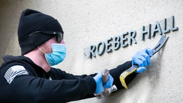 """An unidentified workman takes down lettering from a University of California, Berkeley building on Jan. 26, 2021 after officials agreed to """"unname"""" the building for former anthropology Professor Alfred Kroeber. The professor's studies of California tribes and his treatment of an Indigenous man named Ishi in the early 1900s have stirred controversy. (Photo by Irene Yi, UC Berkeley)"""