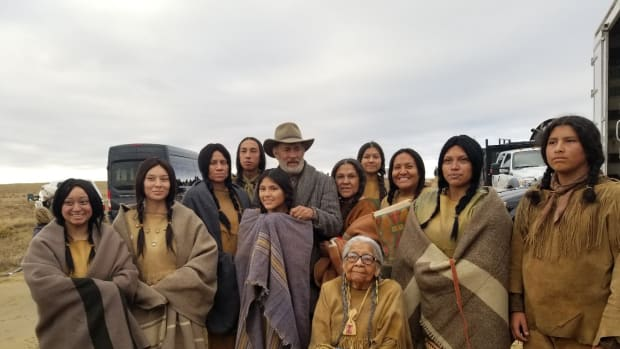 """Tom Hanks (hat) gets his picture with Dorothy WhiteHorse (sitting) and the Kiowa cast of """"News of the World."""" (Photo by Lynda DeLaune via Gaylord News)"""