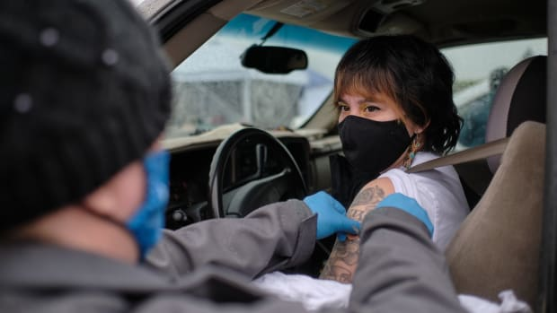Immunizing Pharmacist Amy Valdez puts a bandage on Venus Thornton after vaccinating her at a temporary COVID-19 vaccine site organized by the Siletz Community Health Clinic for tribal members and their families in Salem. (Photo by Alex Milan Tracy for Underscore.news)