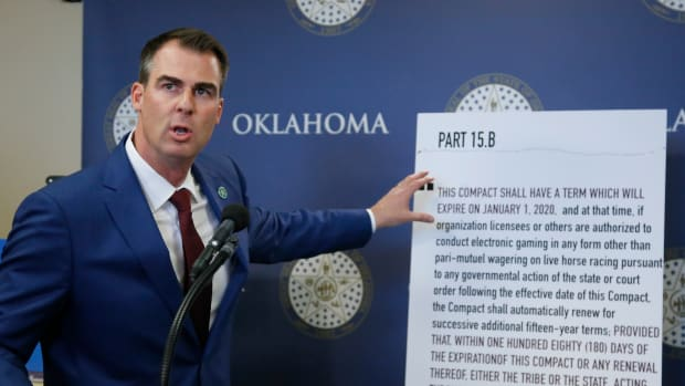 Oklahoma Gov. Kevin Stitt gestures to a sign which addresses the renewal of Tribal Gaming Compacts during a news conference Thursday, Nov. 14, 2019, in Oklahoma City.