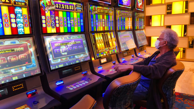 A patron wearing a mask, plays a slot machine at the Seminole Hard Rock Hotel & Casino, Friday, March 20, 2020, in Hollywood, Fla. The Seminole Tribe closed its casinos, the latest virus-related closures affecting a state that is heavily dependent on tourism and consumer spending to pay its bills. (AP Photo/Wilfredo Lee)