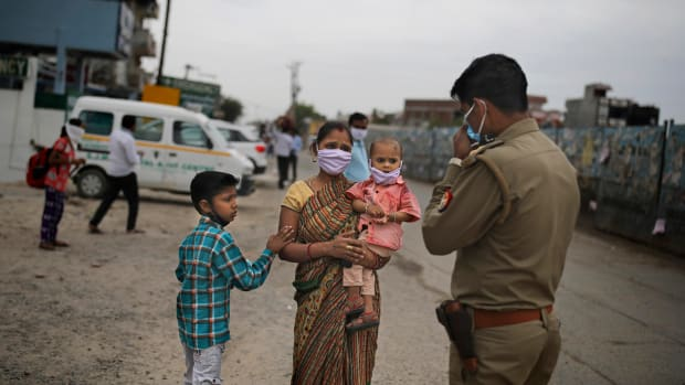An Indian woman pleads in front of a policeman to let her pass a check point hoping to walk to their home with her family, a few hundred kilometers away, as the city comes under lock down in Ghaziabad, on the outskirts of New Delhi, India, Thursday, March 26, 2020. Some of India's legions of poor and people suddenly thrown out of work by a nationwide stay-at-home order began receiving aid distribution Thursday, as both the public and private sector work to blunt the impact of efforts to curb the coronavirus pandemic. Untold numbers of them are now out of work and many families have been left struggling to eat. (AP Photo/Altaf Qadri)