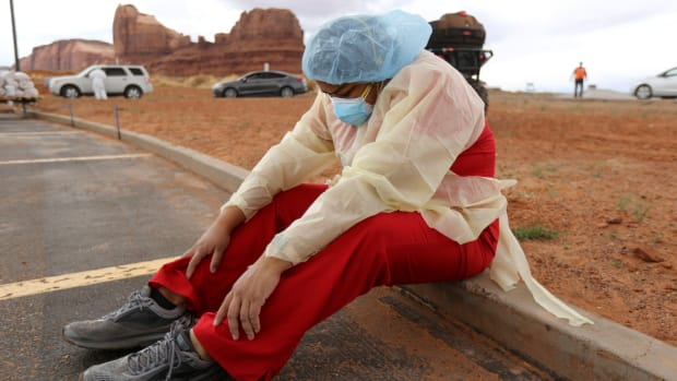 """""""My feet hurt,"""" says Denise Begaye, an X-ray technician with the Monument Valley Health Center, as she sits on a curb and takes a break from COVID-19 testing outside of the center in Oljato-Monument Valley, San Juan County on Thursday, April 16, 2020. The mobile testing team tested 581 people on Thursday. (Photo by Kristin Murphy, Deseret News via AP)"""