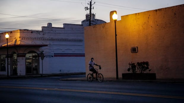 A man riding a bicycle down an empty street wears a protective mask amid the COVID-19 coronavirus outbreak on Friday, April 17, 2020, in Dawson, Ga. In the impoverished southwest corner of Georgia the virus quietly climbed to having some of the country's worst per capita death rates from COVID-19. The underlying health conditions that make COVID-19 so deadly are more prevalent for African American people and for rural people, and they are mostly both, so doubly disadvantaged when the virus tore through town. (AP Photo/Brynn Anderson)