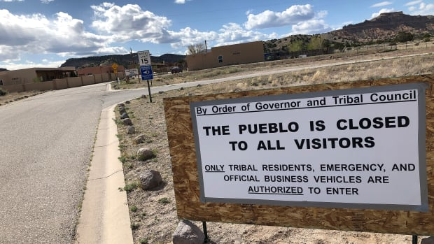 A sign at the Native American community of San Idefonso Pueblo, N.M., urges visitors to stay away as small Indian pueblos throughout the state seek to shield themselves from COVID-19 infection, Thursday, April 23, 2020. San Ildefonso was invited to participate in universal testing by state health officials. (AP Photo/Morgan Lee)
