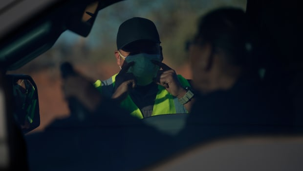 An officer with the Navajo Nation Police talks to a driver at a roadblock in Tuba City, Ariz., on the Navajo reservation on April 22, 2020. The roadblock was to inform residents of evening and weekend curfews, hand washing, and wearing a face mask to help control the spread of COVID-19. (AP Photo/Carolyn Kaster)