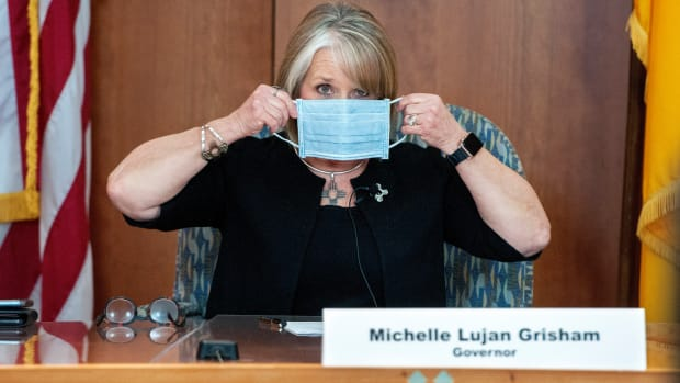 New Mexico Gov. Michelle Lujan Grisham puts on her face mask when not speaking during an update on the COVID-19 outbreak in the state during an April 15, 2020, news conference in the state Capitol in Santa Fe, N.M. New Mexico Republicans and sheriffs are asking U.S. Attorney General William Barr to look into Gov. Michelle Lujan Grisham's health orders aimed at stopping the spread of COVID-19. They allege the order, which has closed several small businesses, violates residents' civil rights. (Eddie Moore/The Albuquerque Journal via AP, Pool, File)