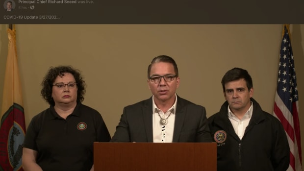 On March 27 Eastern Band of Cherokee Indians Principal Chief Richard Sneed announced the first case of COVID-19 in a part-time resident on the tribe's land while Secretary of Public Health and Human Services Vickie Bradley and CEO of the Cherokee Indian Hospital Authority Casey Cooper join the chief in a press conference. As of Monday morning the tribe has confirmed 43 cases. Video screen shot from Principal Chief Sneed's Facebook page.