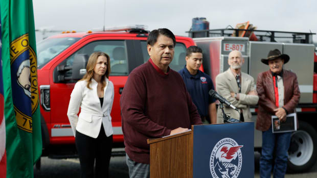 Rodney Cawston,, second from left, Chairman of the Confederated Tribes of the Colville Nation, talks to reporters Wednesday, Oct. 10, 2018, as Washington state Public Lands Commissioner Hilary Franz, left, looks on during a news conference at the Dept. of Natural Resources' aviation hanger in Tumwater, Wash. Franz, Cawston and other officials are asking the Legislature for an increase in DNR budget funding for wildfire response and prevention for the two-year budget cycle that begins in 2019. (AP Photo/Ted S. Warren)