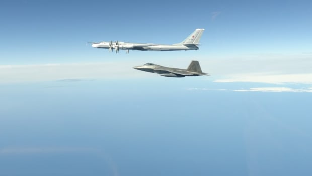 PETERSON AIR FORCE BASE, Colo. - A North American Aerospace Defense Command F-22 Raptor flies next to a Russian Tu-95 bomber during an intercept in the Alaskan Air Defense Identification Zone June 16, 2020. NORAD employs a layered defense network of radars, satellites, and fighter aircraft to identify aircraft and determine the appropriate response. (Photo by NORAD public affairs)