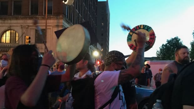 As Trump's rally concludes, crowds are again building in the streets. An Indigenous group drums as protesters begin surrounding a group of police vehicles in the road.