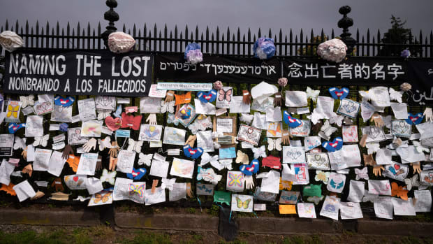 "In this Thursday, May 28, 2020 file photo, a fence outside Brooklyn's Green-Wood Cemetery is adorned with tributes to victims of COVID-19 in New York. The memorial is part of the Naming the Lost project which attempts to humanize the victims who are often just listed as statistics. The wall features banners that say ""Naming the Lost"" in six languages — English, Spanish, Mandarin, Arabic, Hebrew, and Bengali. (AP Photo/Mark Lennihan)"