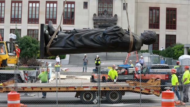 Workers remove the Christopher Columbus statue from the Broad Street side of Columbus City Hall in Columbus, Ohio, Wednesday, July 1, 2020. The city says it will be replaced with a different statue or artwork that reflects diversity. (Doral Chenoweth/The Columbus Dispatch via AP)