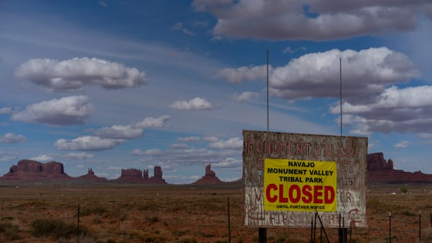 "A sign reads ""Navajo Monument Vally Tribal Park Closed Until Further Notice"" posted at the entrance of Monument Valley in Oljato-Monument Valley, Utah, on the Navajo reservation April 19, 2020. (FILE: AP Photo/Carolyn Kaster)"