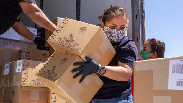 Sergeant Sharyl Chief of the Tuba City Department of Corrections unloading a truck load of canned water donated by Jason Mamoa's water company, Mananal, to the Navajo & Hopi elders. (Photo by Deidra Peaches, Founder of Paper Rocket Productions)