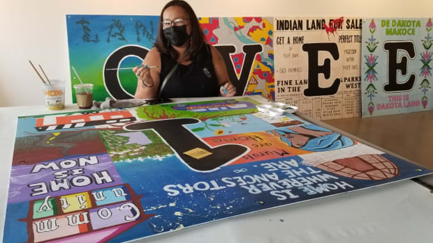 """Muralist Thomasina Topbear, Santee Dakota and Oglala Lakota, helps paint an panelt for art installation, """"Never Homeless Before 1492,"""" that is set to be installed in fall 2021 at the site of a former Indigenous homeless encampment known as """"The Wall of Forgotten Natives"""" in Minneapolis, Minnesota. The installation is being coordinated by artist Courtney Cochran. (Photo courtesy of Courtney Cochran)"""