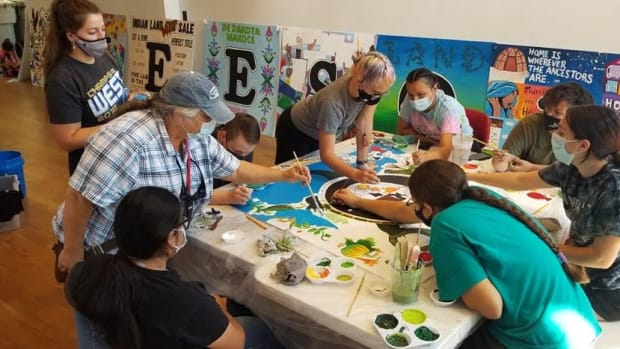 """Phoebe Young, top left, a Saginaw Chippewa descendant, joins participants in the nonprofit Dream of Wild Health's summer youth programs as they paint a panel for an art installation on Indigeneous homelessness set to go up in the fall of 2021. The exhibit, """"Never Homeless Before 1492,"""" is being coordinated by artist Courtney Cochran. It will be installed at the site of a former homeless encampment known as """"The Wall of Forgotten Natives,"""" in Minneapolis, Minnesota. (Photo by Courtney Cochran, courtesy of Dream of Wild Health)"""
