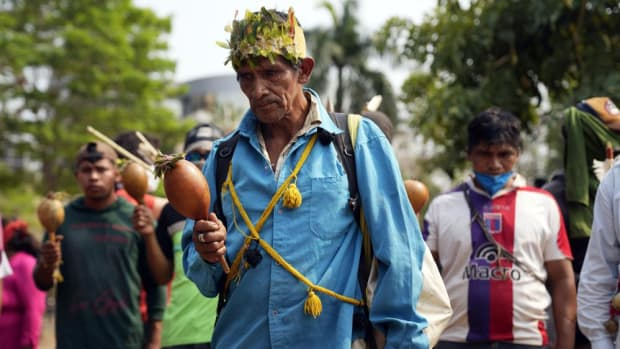 An Indigenous Ava Guarani Shaman prays during a protest by several Indigenous groups against a proposed bill that criminalizes land invasions, outside Congress in Asuncion, Paraguay, Wednesday, Sept. 29, 2021. If the bill passes it would affect several Indigenous communities who reside on improvised settlements pending the restitution of their lands. (AP Photo/Jorge Saenz)