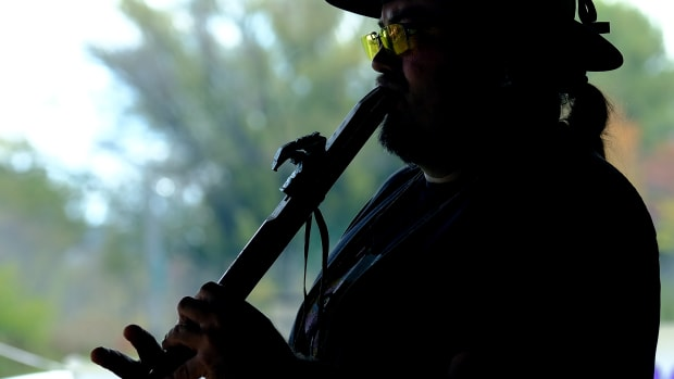 Michael Laughing Fox Charette, a citizen of the Red Cliff Band of Ojibwe, plays a traditional flute during a water protector celebration on Madeline Island in Wisconsin on Oct. 2, 2021. (Photo by Mary Annette Pember/Indian Country Today)