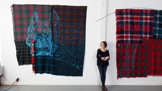 Seneca artist Marie Watt stands in her Portland, Oregon, studio in 2016 with a two-panel work featuring a nursing wolf, made from reclaimed blankets and thread. (Photo by Robbie McLaran, courtesy of Marie Watt)