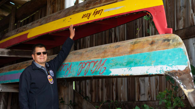 Lummi Nation Chairman Lawrence Solomon points to the Lady Rose, a canoe his mother used to paddle, at the Tribe's canoe shed on the Stommish grounds, land that his family owned for generations, on Friday, Oct. 1, 2021. His great-grandmother Edith Jones and her husband Vic held the first Stommish in 1946 in honor of their two sons, Bill and Stanley Solomon, and other Lummi veterans who returned home from World War II. Chairman Solomon, a Navy veteran and leader of the Blackhawk Singers, is currently in his second year as chairman for the Tribe. (Photo by Natasha Brennan, McClatchy)