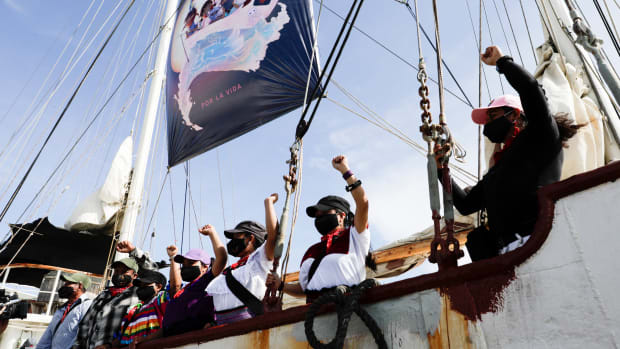 "A delegation of the Zapatista Army of National Liberation, EZLN, say goodbye from a ship as they depart to Europe from Isla Mujeres, Quintana Roo state, Mexico, Sunday, May 2, 2021. The rebel delegation says they are planning the trip to ""invade"" Spain, as Mexico marks the anniversary of its 1519-1521 Spanish Conquest. (AP Photo/Eduardo Verdugo)"