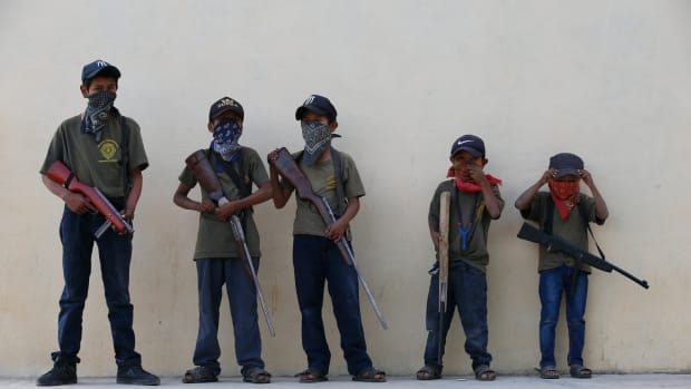 """Children hold their training weapons, some real and some fake, during a display for the media designed to attract the federal government's attention to the dangers of organized crime that their town negotiates daily in Ayahualtempa, Guerrero state, Mexico, Wednesday, April 28, 2021. International organizations have condemned the """"recruitment"""" of children and warned of the effects. (AP Photo/Marco Ugarte)"""