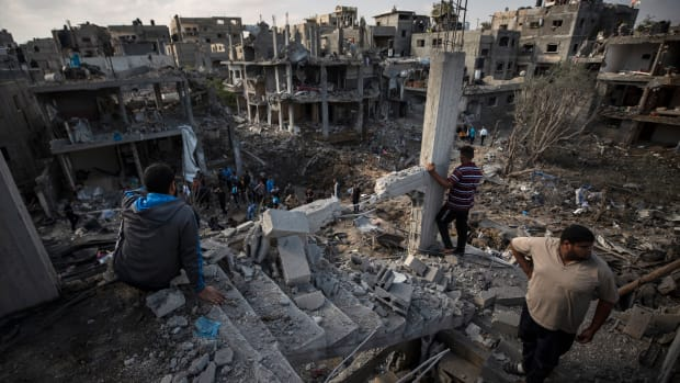 Palestinians inspect their destroyed houses following overnight Israeli airstrikes in town of Beit Hanoun, northern Gaza Strip, Friday, May 14, 2021. (AP Photo/Khalil Hamra)