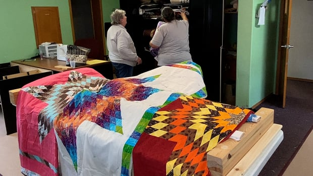 Some star quilts for high school graduates from the Bad River Band of Lake Superior Chippewa tribe in Wisconsin are already finished. Volunteer seamstresses are hard at work in their sewing room in March 2021 creating a handmade quilt for each graduate. (Photo by Mary Annette Pember)