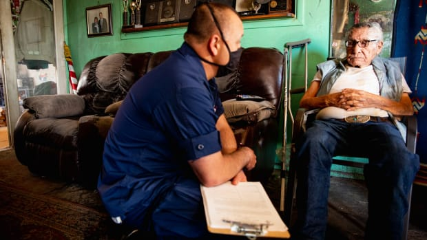 Justin Tafoya, a registered nurse serving as a public information officer, talks to Lafe Altaha about his health before a nurse checks Altaha's vital signs at his home in Whiteriver, Ariz., on March 17, 2021. (Photo by Alberto Mariani/Cronkite News)